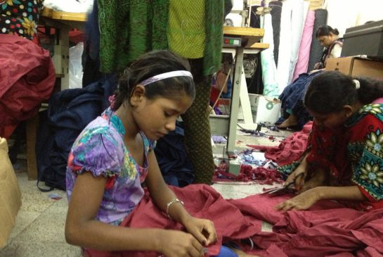 A Young Girl Sews Fabric for a Clothes Retailer