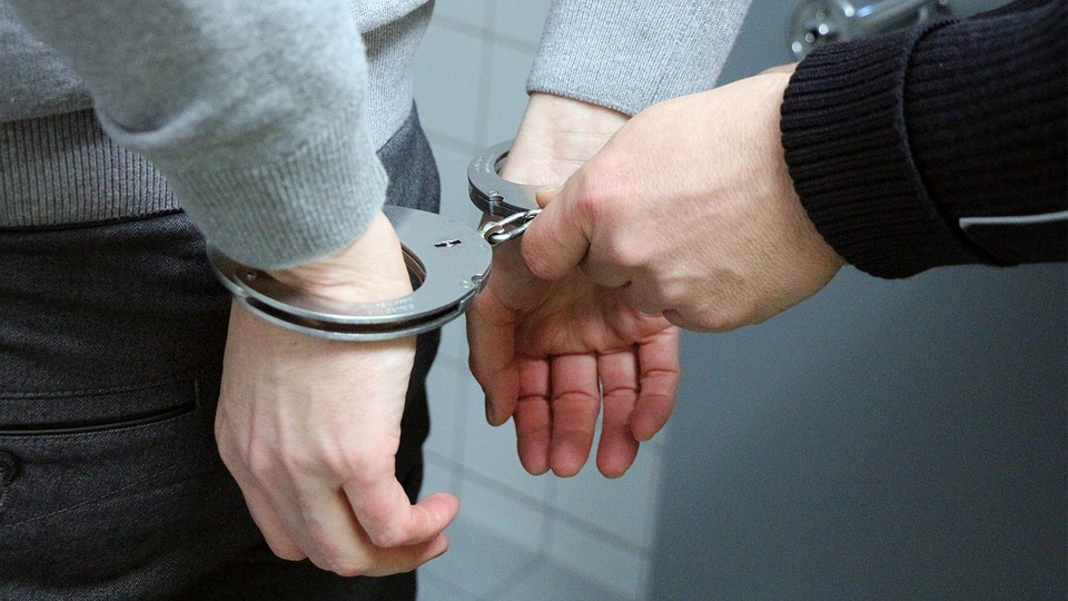 Individual being handcuffed for facilitating tax evasion