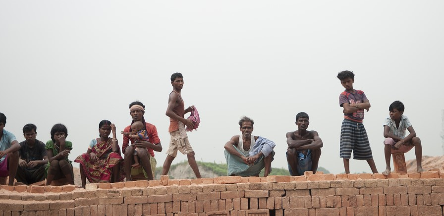 A group of people being kept as modern slaves, including a mother with a baby