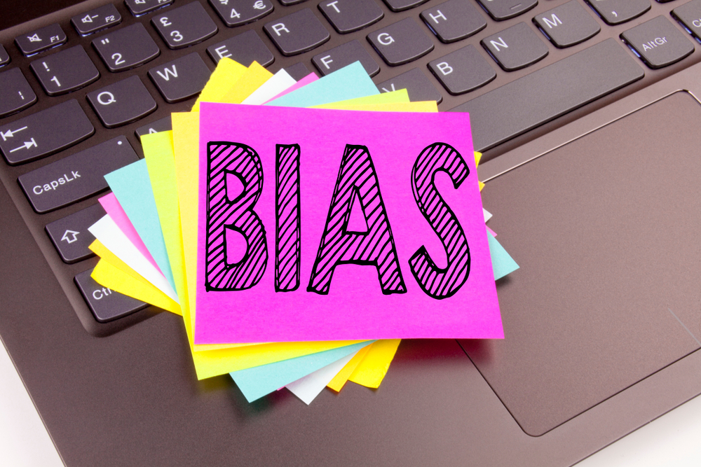 "Post-it notes on a laptop saying ""bias"""