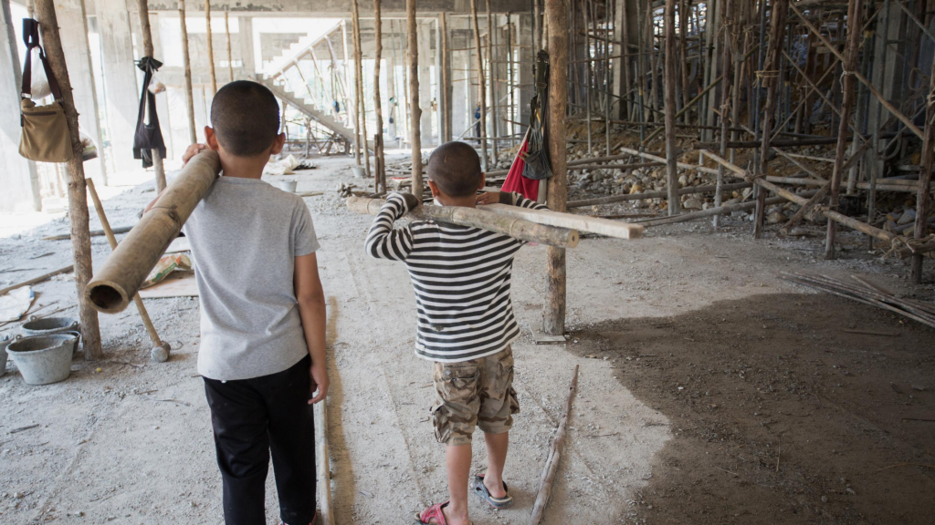 Two young boys carrying heavy poles in a construction site